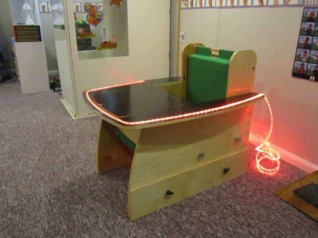 Side view of sensory adapted task desk with lighting and adjustable table top