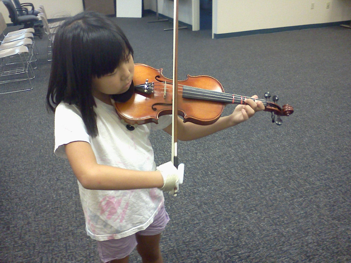 Young violinist with bow holder